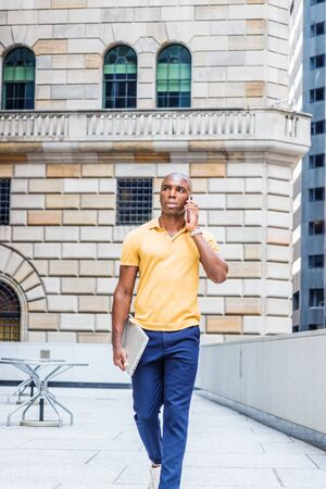 Young African American Business Man traveling, working in New York City, wearing yellow short sleeve shirt, blue pants, carrying laptop computer, walking outside office building, talking on cell phone,