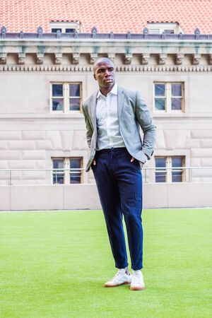 Young African American Man Street Fashion in New York City. Black college student with short hair, wearing gray patterned blazer, white shirt, blue pants, sneakers, standing on green lawn on campus.