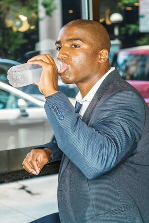 Young Handsome African American Businessman with afro short hair, traveling in New York City, wearing blue blazer, sitting inside a coffee shop, drinking bottle of water, relaxing, taking work break.