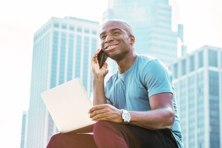 Young African American Businessman traveling, working in New York, wearing blue T shirt, sitting in front of business district, working on laptop computer, talking on cell phone, looking up, smiling.