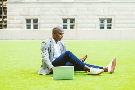 Young African American Businessman working in New York City, wearing gray patterned blazer, white shirt, blue pants, sneakers, sitting on green lawn, working on laptop computer, texting on cell phone. Stock fotó