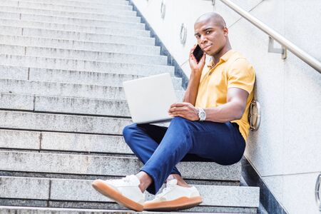 Way to Success. Young African American Man working in New York, wearing yellow shirt, blue pants, sneakers, sitting on stairs outside office building, talking on cell phone, working on laptop computer