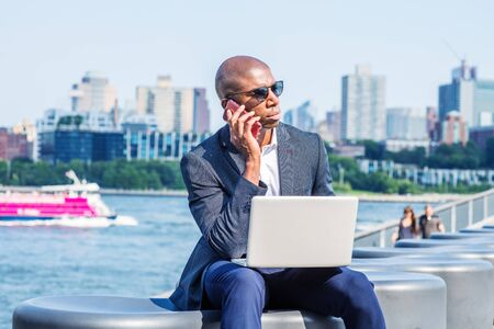 Young African American Businessman traveling, working in New York, wearing blue blazer, sunglasses, sitting by East River, working on laptop computer, talking on cell phone. Brooklyn on far background Stock fotó