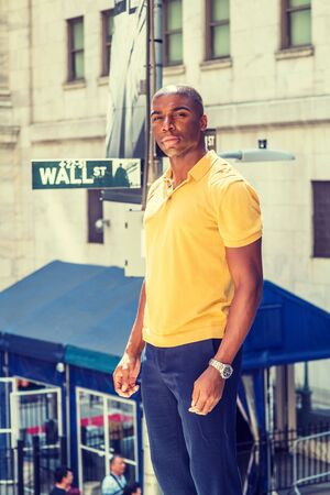 Young African American man traveling in New York City. Wearing yellow short sleeve shirt, young black college student standing on Wall Street outside office, looking forward, confident, successful.
