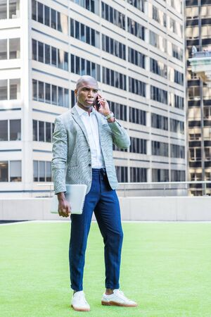 Young African American Businessman Street Fashion in New York City, wearing gray patterned blazer, white shirt, blue pants, sneakers, carrying laptop computer, standing on green lawn, talking on phone
