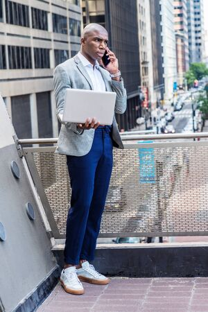 Young African American man wearing gray patterned blazer, blue pants, white sneakers, standing by railing on balcony, facing street with high buildings, working on laptop computer, talking on phone.