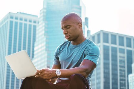 Young African American Businessman with afro short hair, traveling, working in New York, wearing blue T shirt, sitting in front of business district, looking down, reading, working on laptop computer.
