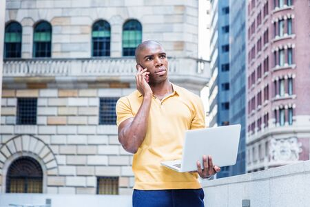 Working anywhere. Young African American Business Man working in New York City, wearing yellow short sleeve shirt, standing outside office building, talking on cell phone, working on laptop computer.