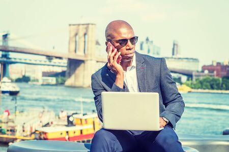 African American Businessman traveling, working in New York, wearing blue blazer, sunglasses, sitting by river, working on laptop computer, talking on phone. Brooklyn, Manhattan bridge on background.