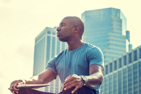 Young African American man traveling in New York City. Wearing gray T shirt, holding laptop computer, young black college student sitting in front of business district, looking, relaxing, thinking. Stock fotó