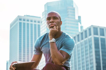Young African American man traveling, working in New York City, wearing gray T shirt, holding laptop computer, sitting in front of business district, hand touching chin, looking, relaxing, thinking.