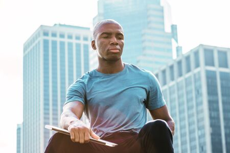 Young African American man traveling in New York City. Wearing gray T shirt, holding laptop computer, young black college student sitting in front of business district, looking down, sad, thinking. Stock fotó