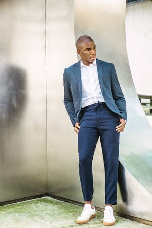 Portrait of Young African American Man in New York City. Wearing blue blazer, white shirt, blue pants, white sneakers, young black college student standing against silver metal wall on campus, think.
