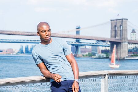 I missing you, waiting for you. Young African American Man traveling in New York City, wearing gray T shirt, standing by East River, looking forward. Manhattan, Brooklyn bridges on background.