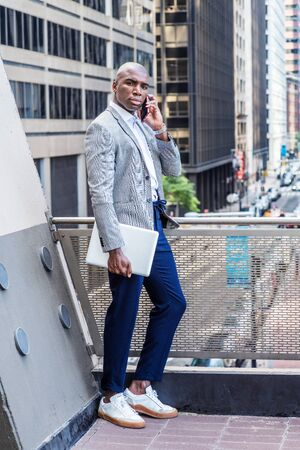 Wearing gray patterned blazer, blue pants, white sneakers, holding laptop computer, young African American man standing by railing on balcony, facing street with high buildings, talking on cell phone.