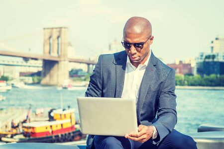 African American Businessman with afro short hair, traveling, working in New York, wearing blue blazer, sunglasses, sitting by river, working on laptop computer. Brooklyn bridge, boat on background.
