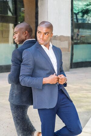 Portrait of Young African American Man in New York City. Wearing blue blazer, white shirt, blue pants, young black college student standing against metal mirror on street, looking away, thinking. Stock fotó