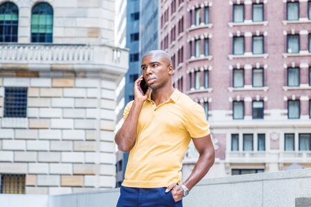 Young African American Man Street Fashion in New York City. Wearing yellow short sleeve shirt, young black college student with short hair, standing outside office building, talking on cell phone.