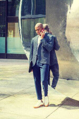 Young African American Businessman traveling, working in New York, wearing blue blazer, pants, white sneaker, carrying black briefcase, standing against metal mirror on street, talking on cell phone. Stock fotó