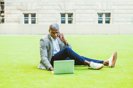Young African American Businessman working in New York City, wearing gray patterned blazer, white shirt, blue pants, sneakers, sitting on green lawn, working on laptop computer, talking on cell phone.