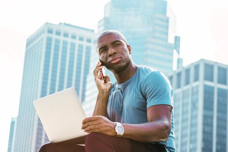 Young African American Businessman traveling, working in New York, wearing blue T shirt, sitting in front of business district, working on laptop computer, talking on cell phone, looking, thinking. Stock fotó
