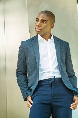 Portrait of Young African American Man in New York City. Wearing blue blazer, white shirt, blue pants, young black college student standing against silver metal wall on campus, looking away, thinking.