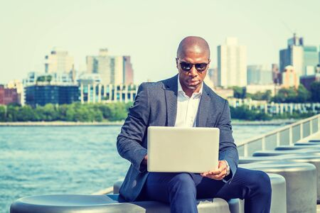 Young African American Businessman with afro short hair, traveling, working in New York, wearing blue blazer, sunglasses, sitting by river, working on laptop computer. Brooklyn on far background. Stock fotó