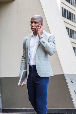 Young African American Business Man traveling, working in New York City, wearing gray blazer, blue pants, carrying laptop computer, walking outside office building, talking on cell phone, Stock fotó