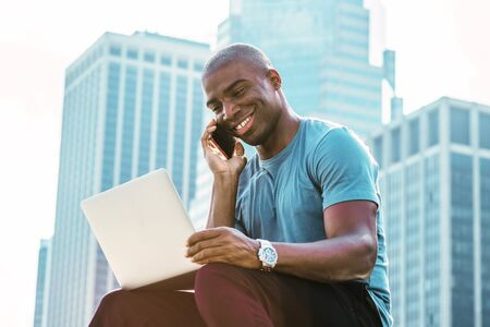 Young African American Businessman traveling, working in New York, wearing blue T shirt, sitting in front of business district, looking down, working on laptop computer, talking on cell phone, smiling