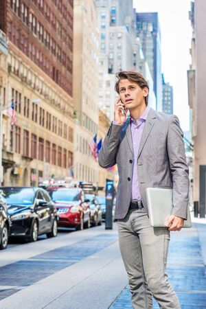 Young Businessman traveling, working in New York, wearing gray blazer, patterned shirt, holding laptop computer, standing on street in Manhattan, talking on cell phone, looking up, frowned, worried. Foto de archivo - 134557159