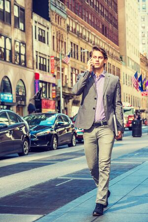 Young Businessman traveling, working in New York, wearing gray blazer, patterned shirt, pants, black leather shoes, holding laptop computer, walking on street in Manhattan, talking on cell phone. Foto de archivo - 134557350