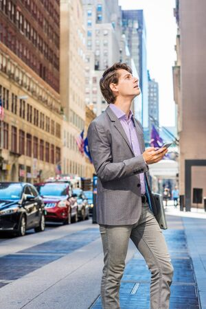 Young Businessman traveling, working in New York, wearing gray blazer, patterned shirt, carrying laptop computer, holding cell phone, standing on street in Manhattan, looking up, thinking. Foto de archivo - 134557353