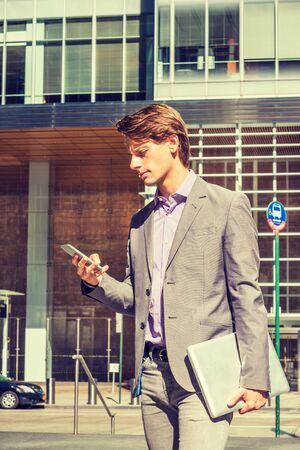Young Businessman traveling, working in New York, wearing gray blazer, patterned shirt, holding laptop computer, walking on street in Manhattan, texting on cell phone. Foto de archivo - 134557355