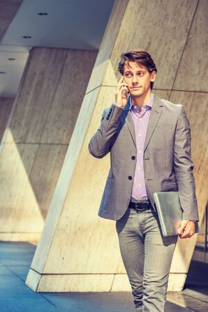Young Businessman working in New York, wearing gray blazer, patterned shirt, holding laptop computer, walking out from office building to street, talking on cell phone. Foto de archivo - 134557364
