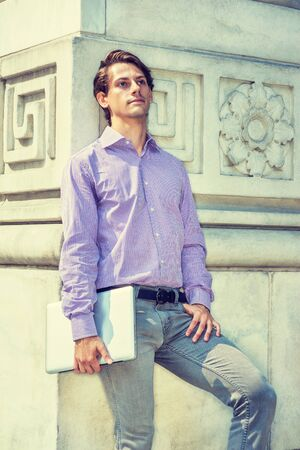 Young Handsome Businessman thinking, relaxing outside in New York, wearing patterned shirt, carrying laptop computer, standing against vintage wall, sad, lost in thought. Filtered effect. 写真素材