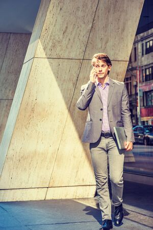 Young Businessman working in New York, wearing gray blazer, patterned shirt, pants, black leather shoes, holding laptop computer, walking out from office building to street, talking on cell phone. Foto de archivo - 134557367