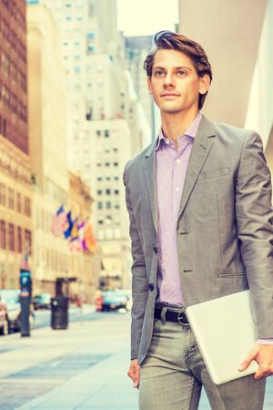 Young Businessman traveling, working in New York, wearing gray blazer, patterned shirt, holding laptop computer, walking on street in Manhattan, confidently looking forward. Filtered effect.