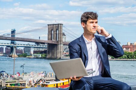 Young Businessman traveling, working in New York City, wearing blue suit, white shirt, sitting by river, working on laptop computer, talking on cell phone. Manhattan, Brooklyn bridges on background. Foto de archivo - 134557303