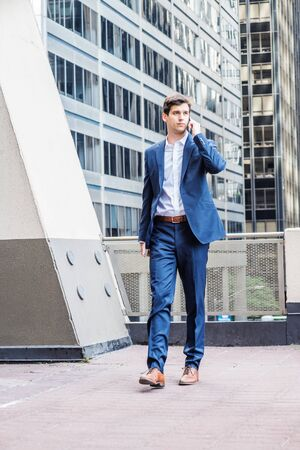 Young American Businessman working in New York City, wearing blue suit, white shirt, brown leather shoes, holding laptop computer, talking on cell phone, walking on balcony outside office building. Foto de archivo - 134557313