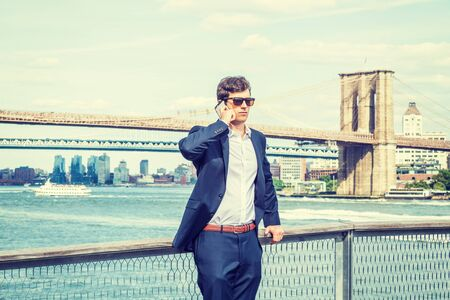 Young American Man traveling, relaxing in New York City, wearing blue suit, white shirt, sunglasses, standing by East River, talking on cell phone. Manhattan, Brooklyn bridges, boats on background.
