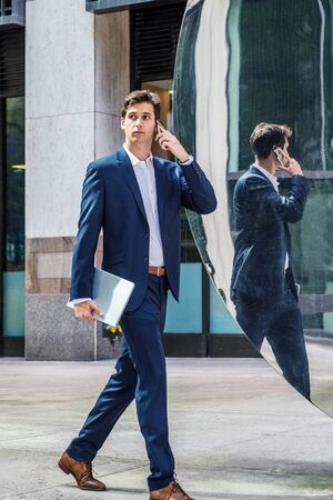 Young businessman traveling, working in New York City, wearing blue suit, white shirt, holding laptop computer, walking on street passing by metal mirror, looking around, talking on cell phone. Foto de archivo - 134557323