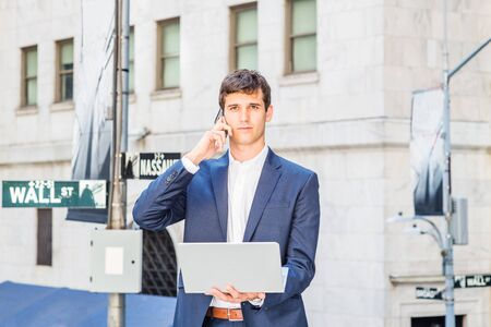 Young Man traveling, working in New York City, wearing blue suit, white shirt, standing on street outside office building by Wall Street sign, working on laptop computer, talking on cell phone. Foto de archivo - 134557324