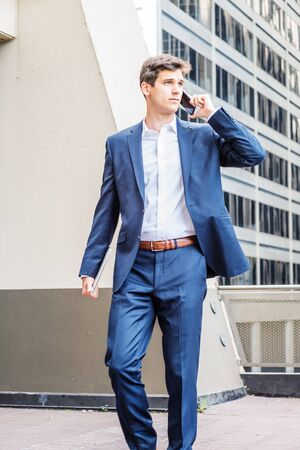 Young American College Student studying, working in New York City, wearing blue suit, white shirt, holding laptop computer, talking on cell phone, walking on balcony outside office building on campus. Foto de archivo - 134557326