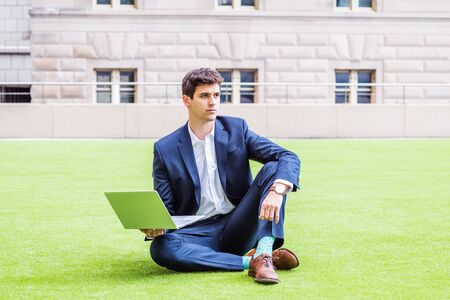 Young college student studying, working in New York City, wearing blue suit, white shirt, brown leather shoes, sitting on green lawn outside office building on campus, working on laptop computer. Foto de archivo - 134557328