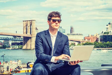Young Businessman traveling, working in New York City, wearing blue suit, white shirt, sunglasses, sitting by East River, working on laptop computer. Manhattan, Brooklyn bridges on background. Stock fotó