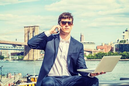 Young Businessman traveling, working in New York City, wearing blue suit, white shirt, sitting by river, working on laptop computer, talking on cell phone. Manhattan, Brooklyn bridges on background. Foto de archivo - 134557256