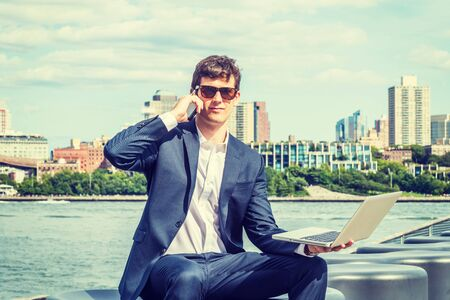 Young Businessman traveling, working in New York City, wearing blue suit, white shirt, sunglasses, sitting by river, working on laptop computer, talking on cell phone. Brooklyn buildings on background. Foto de archivo - 134557262