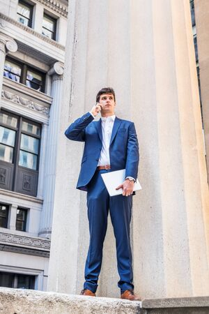 Modern daily life. Young businessman traveling, working in New York City, wearing blue suit, white shirt, holding laptop computer, standing on street outside office building, talking on cell phone. Foto de archivo - 134557214