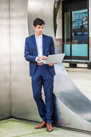 Young college student studying, working in New York City, wearing blue suit, white shirt, brown leather shoes, standing against silver metal wall on street, looking down, working on laptop computer. Foto de archivo - 134557169