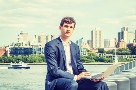 Young American Businessman traveling, working in New York City, wearing blue suit, white shirt, sitting by East River, working on laptop computer, looking, thinking. Brooklyn buildings on background. Foto de archivo - 134557179